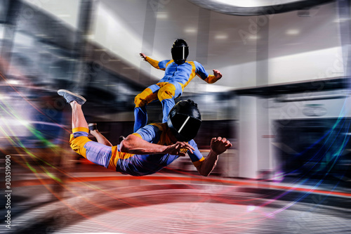 Fototapety, obrazy: I flying. Skydiving in wind tunnel. New skydiving sport in flight technology. Indoor skydiving. Training in wind tunnel. Surfing on people