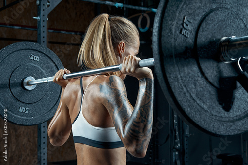 Fotomural Crossfit woman workout Female bodybuilder doing back squats in gym Blonde gettin