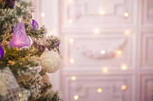 Background From A Christmas Tree Decorated In Blue And Purple Close-up. Greeting Card From A Christmas Tree With Purple Decorations And Copy Space.
