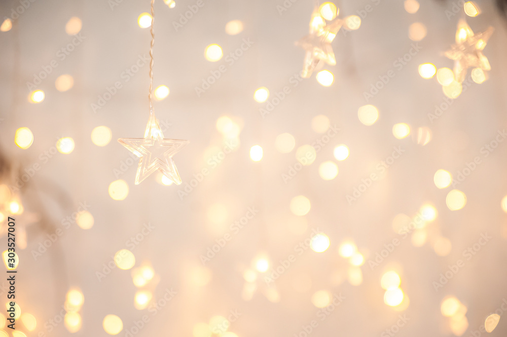 Fototapeta Background of New Year's garlands like stars. Christmas atmosphere with garlands in focus and defocus.