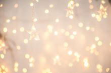 Background Of New Year's Garlands Like Stars. Christmas Atmosphere With Garlands In Focus And Defocus.