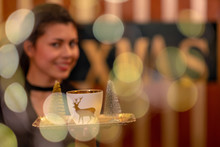 Portrait Of Waitress Carrying A Plate With Christmas Cup In Reindeer Design And X-mas Text Against Spots Of Light