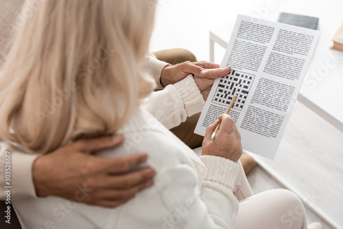 cropped view of senior man hugging wife with pencil and crossword