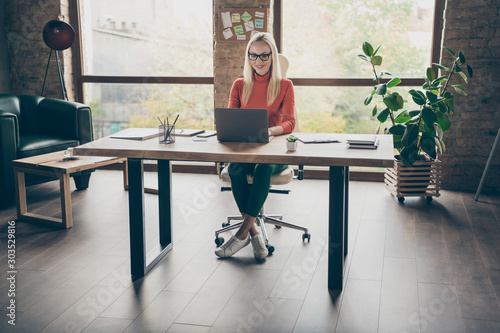 Full size photo of positive woman worker sit table use laptop work on start-up strategy type wear red turtleneck in office loft