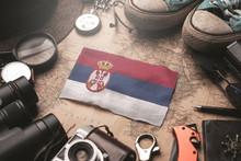 Serbia Flag Between Traveler's Accessories On Old Vintage Map. Tourist Destination Concept.