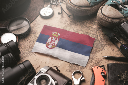 Photo Serbia Flag Between Traveler's Accessories on Old Vintage Map