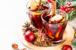 Mulled wine with christmas decorations on white.