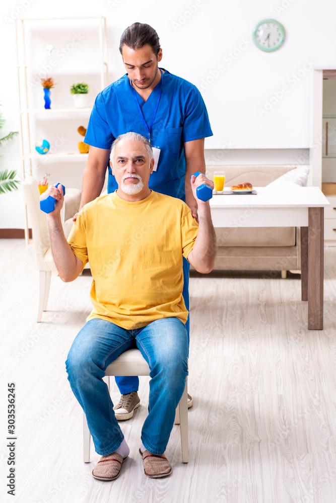 Fototapety, obrazy: Young male doctor visiting old patient at home