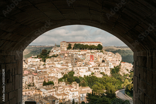 Fotografiet arch near small houses and green trees in ragusa, italy