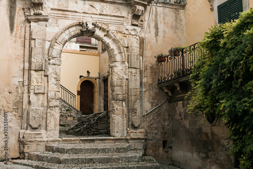 Fotografiet ancient arch in old building near green plants in modica, italy