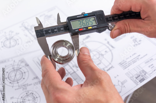 Fototapeta Hands of an engineer measures a metal part with a digital vernier caliper against the background of technical drawings. Quality control of parts machined on a lathe. obraz