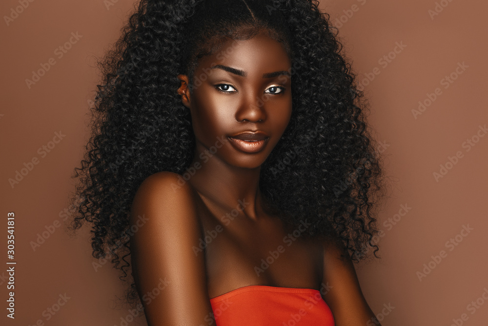 Fototapeta African beautiful woman portrait. Brunette curly haired young model with dark skin and perfect smile