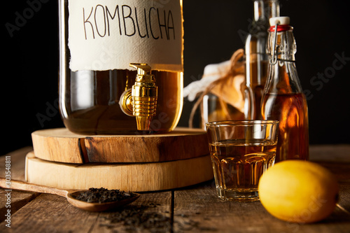 close up view of glass jar with kombucha near lemon, spice and bottles on wooden table isolated on black