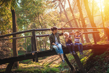 Mother With Kids Enjoys In Sunny Autumn Day In Nature.