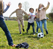 Children Play With Ball Outdoors In Spring