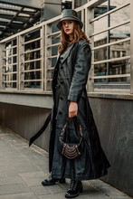 Outdoor Full-length Fashion Portrait Of Young Confident Woman Wearing Long Black Leather Trench Coat, Bucket Hat, Lace Up Ankle Boots, Holding Trendy Small Handbag, Posing In City Street
