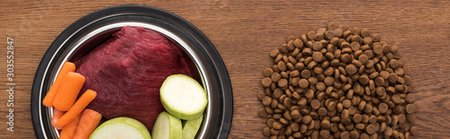 Fototapeta top view of dry pet food near raw vegetables and meat in bowl on wooden table, panoramic shot obraz