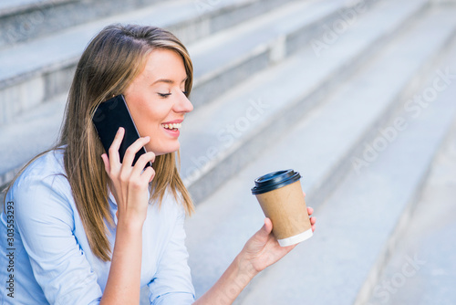 Photo A businesswoman checking email via mobile phone and holding a coffee cup against urban scene