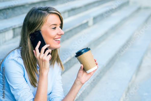 A businesswoman checking email via mobile phone and holding a coffee cup against urban scene Canvas Print