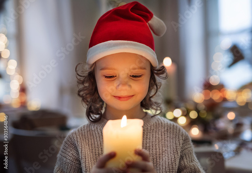 Obraz Cheerful small girl with santa hat indoors at Christmas, holding candle. - fototapety do salonu