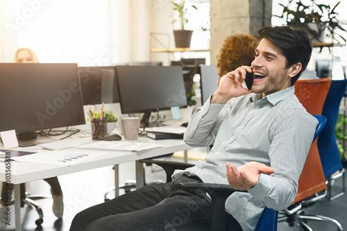 Obraz Cheerful man talking on phone at workplace - fototapety do salonu
