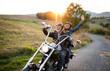 Leinwandbild Motiv A cheerful senior couple travellers with motorbike in countryside.