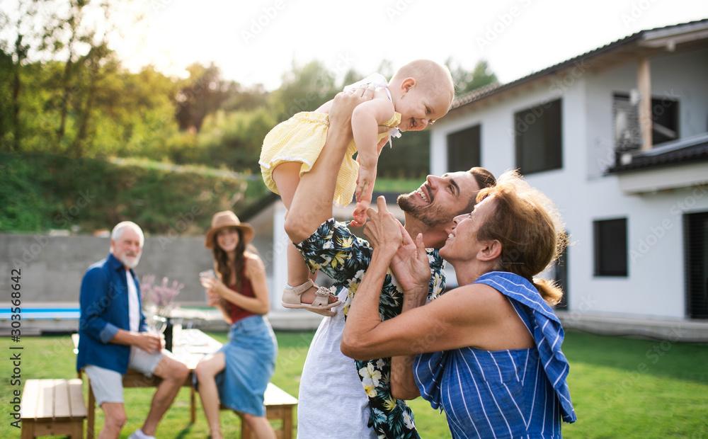 Fototapeta Portrait of multigeneration family outdoors on garden barbecue.