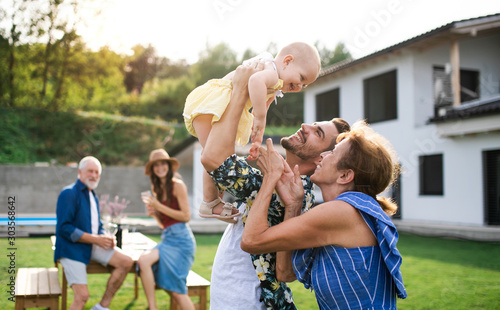Foto  Portrait of multigeneration family outdoors on garden barbecue.