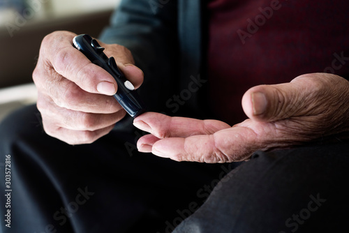 Fotomural  old man about to measure his blood glucose level