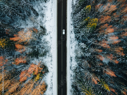 Fotografie, Obraz  Aerial view of snow covered trees in forest and winter country road with a car
