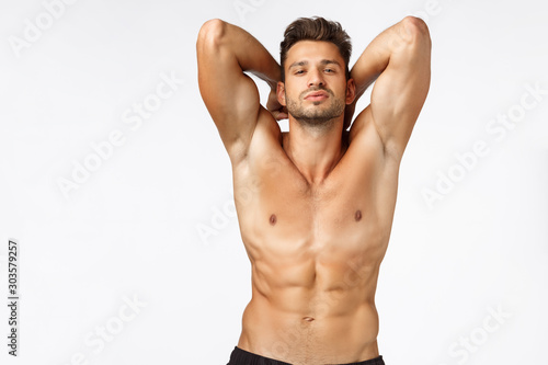 Sexy self-assured, handsome bearded young sportsman, athlete posing showing perf Fototapet