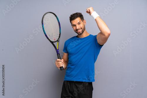 Obraz na płótnie Handsome young tennis player man celebrating a victory