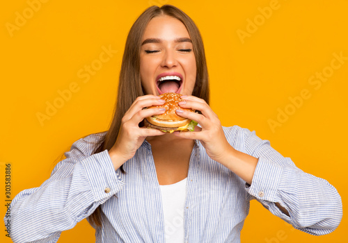 Stampa su Tela  Hungry Woman Biting Burger Standing Over Yellow Background