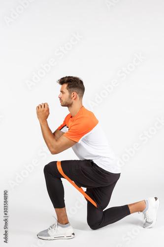 Fotomural Vertical profile shot sportsman perform squats as secure resistance rope between