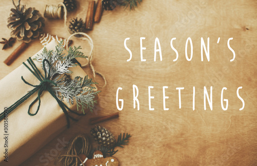 Obraz Season's greetings text sign on stylish rustic christmas gifts box with cedar branch on rural table with pine cones, gingerbread cookies, cotton, cinnamon. Season's greeting card - fototapety do salonu