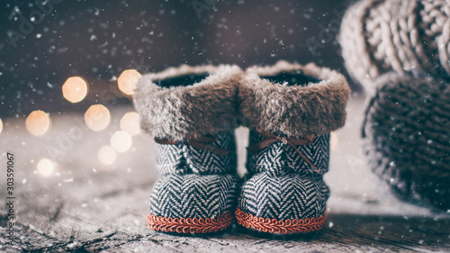 Holiday Christmas Baby Toy Small Boots and Stack Pile of Cozy Knitted Sweaters and Wooden Table Background Slika na platnu