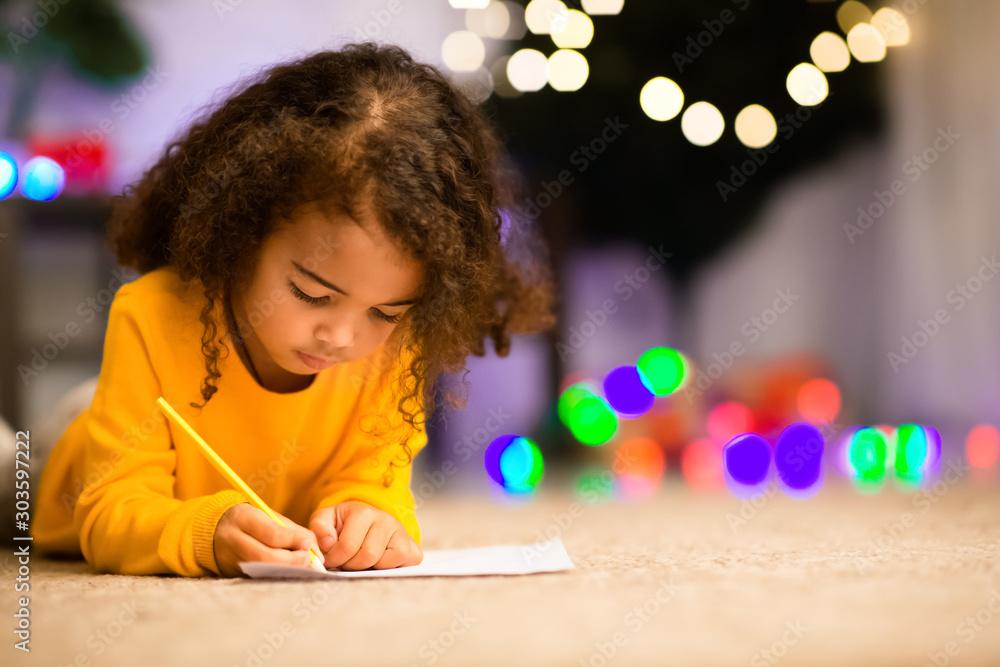 Fototapeta Little black girl drawing on floor near xmas tree