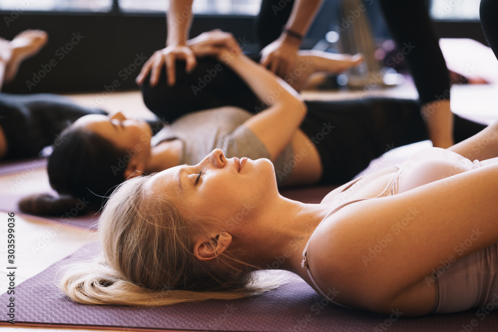 Fototapeta Group of young people in practicing yoga lying  pose on yoga mats with trainer in a gym, Concept of relaxation and meditation.
