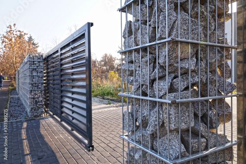 Obraz Gabion. Automatic entrance gate used in combination with a wall made of gabion. - fototapety do salonu