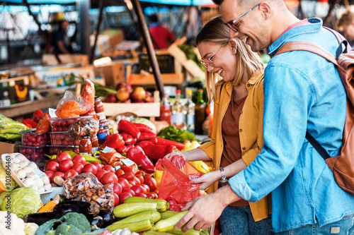 Beautiful young couple buying fresh vegetables on outdoor market.