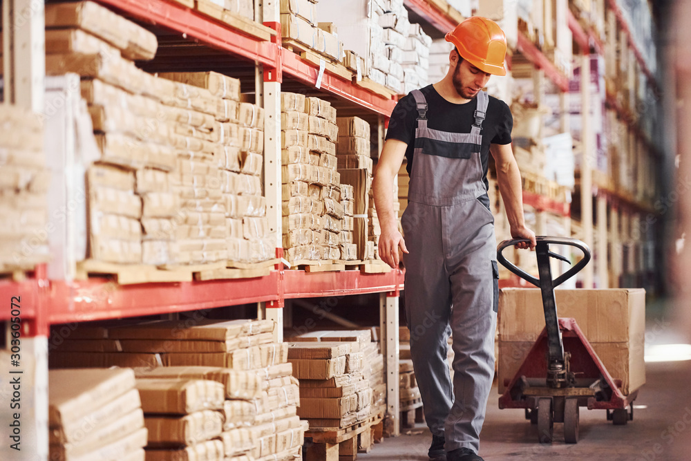 Fototapety, obrazy: Young male worker in uniform is in the warehouse pushing pallet truck