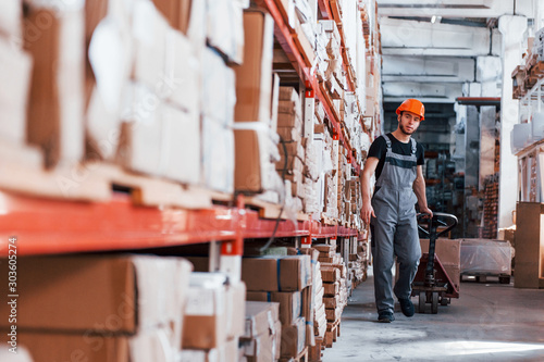 Fototapeta  Young male worker in uniform is in the warehouse pushing pallet truck