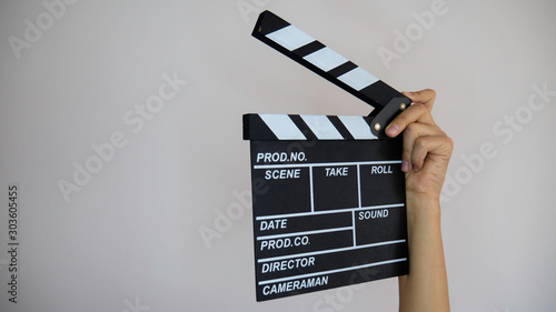 Close up female holding in hand classic director clear empty black film makin...