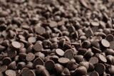 Delicious chocolate chips as background, closeup view
