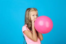 Pretty Little Girl Blowing Pink Balloon On Blue Background