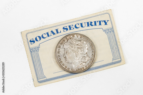 Old Social Security card with antique silver dollar and white background.   #303625289