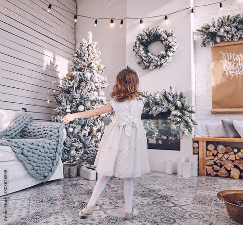 A little girl in an elegant winter white dress is dancing in a room with a Scandinavian interior against the background of a Christmas tree. Children's joy in the New Year holidays - 303626858