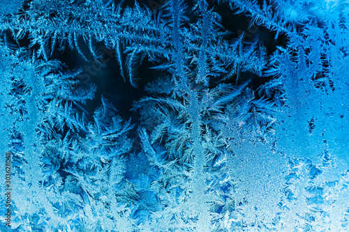 Deurstickers Kristallen Beautiful frozen patterns on glass, macro photo. The concept of winter, the beauty of nature, frost, cold. Abstract background image.