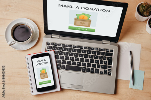 Donation concept on laptop and smartphone screen over wooden table Wallpaper Mural