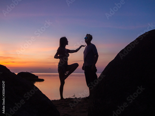 Fototapety, obrazy: Silhouettes of women and men on the beach on a background of colorful sunset